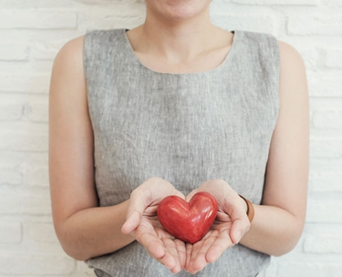 woman holding fake heart for her healthy goals